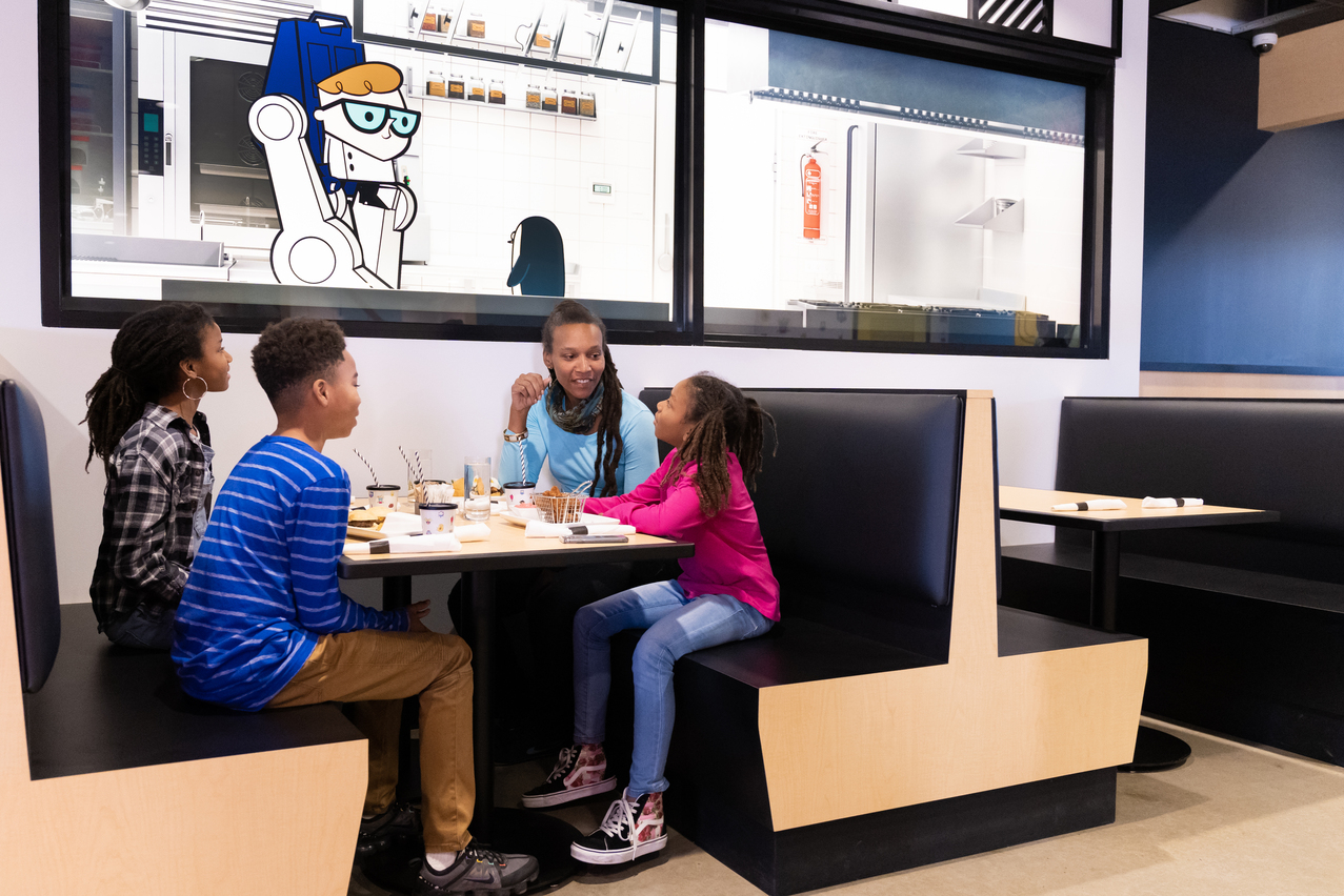 One mom and three kids sitting in a restaurant booth watching cartoon characters walk through a simulated kitchen.