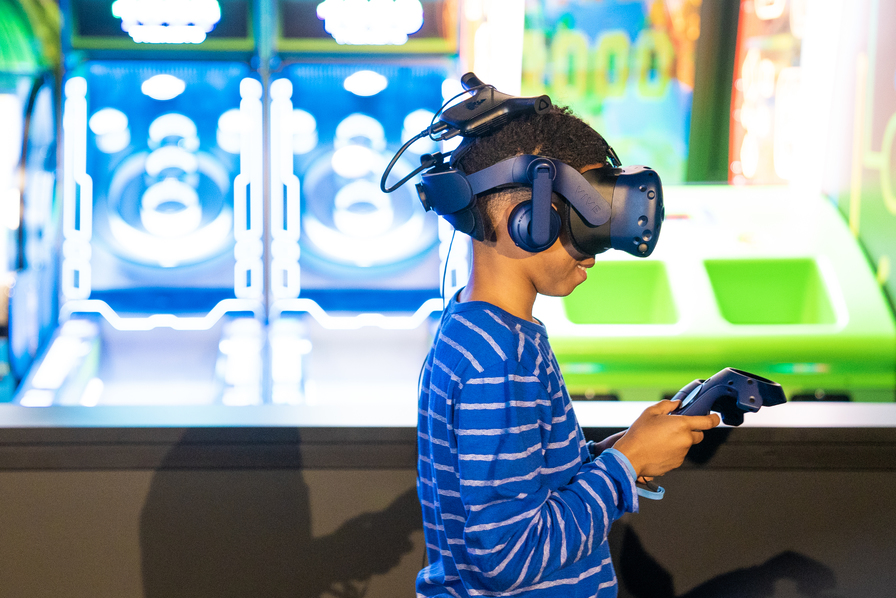Child plays a virtual reality game with a large headset covering his face