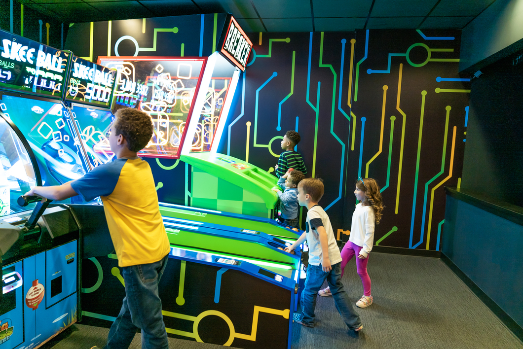 Kids playing skeeball and arcade games in the Omnitrix Arcade