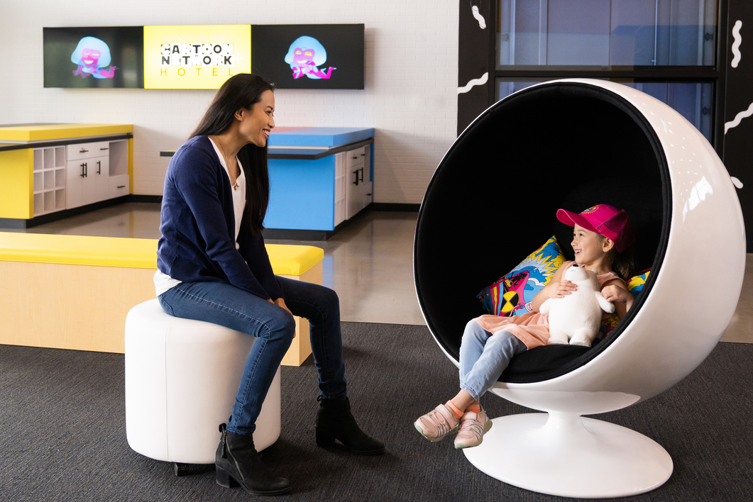 Woman and girl sitting in egg shaped chairs and laughing in the Cartoon Network Hotel lobby