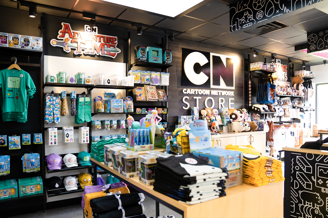 Overview of the Cartoon Network Hotel store, with a variety of colorful plush toys, apparel, souvenirs and more