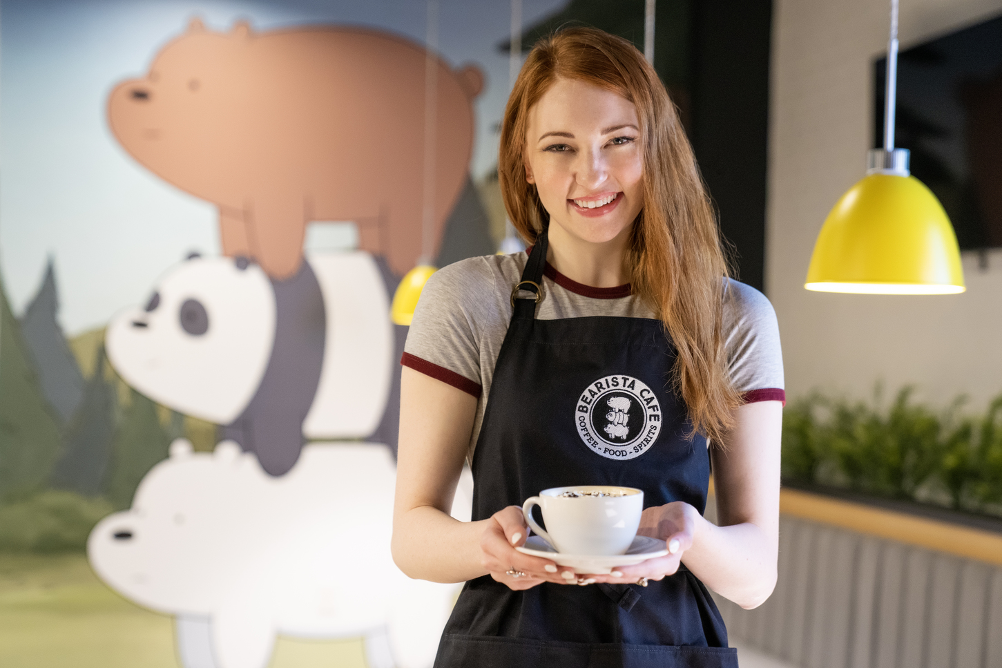 Smiling female barista holds a coffee cup while standing in front of a mural of animated bears