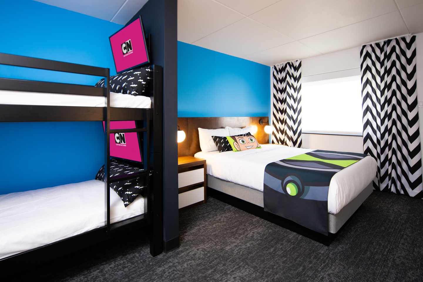 A hotel room with bunk beds and a queen bed in the background