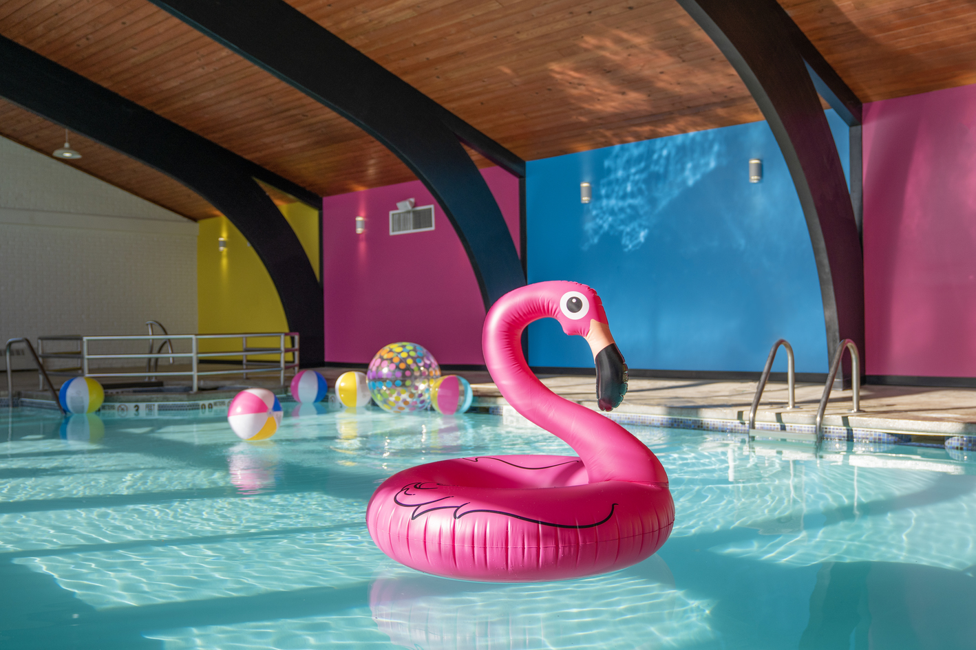 Inflatable pink flamingo floats in an indoor pool