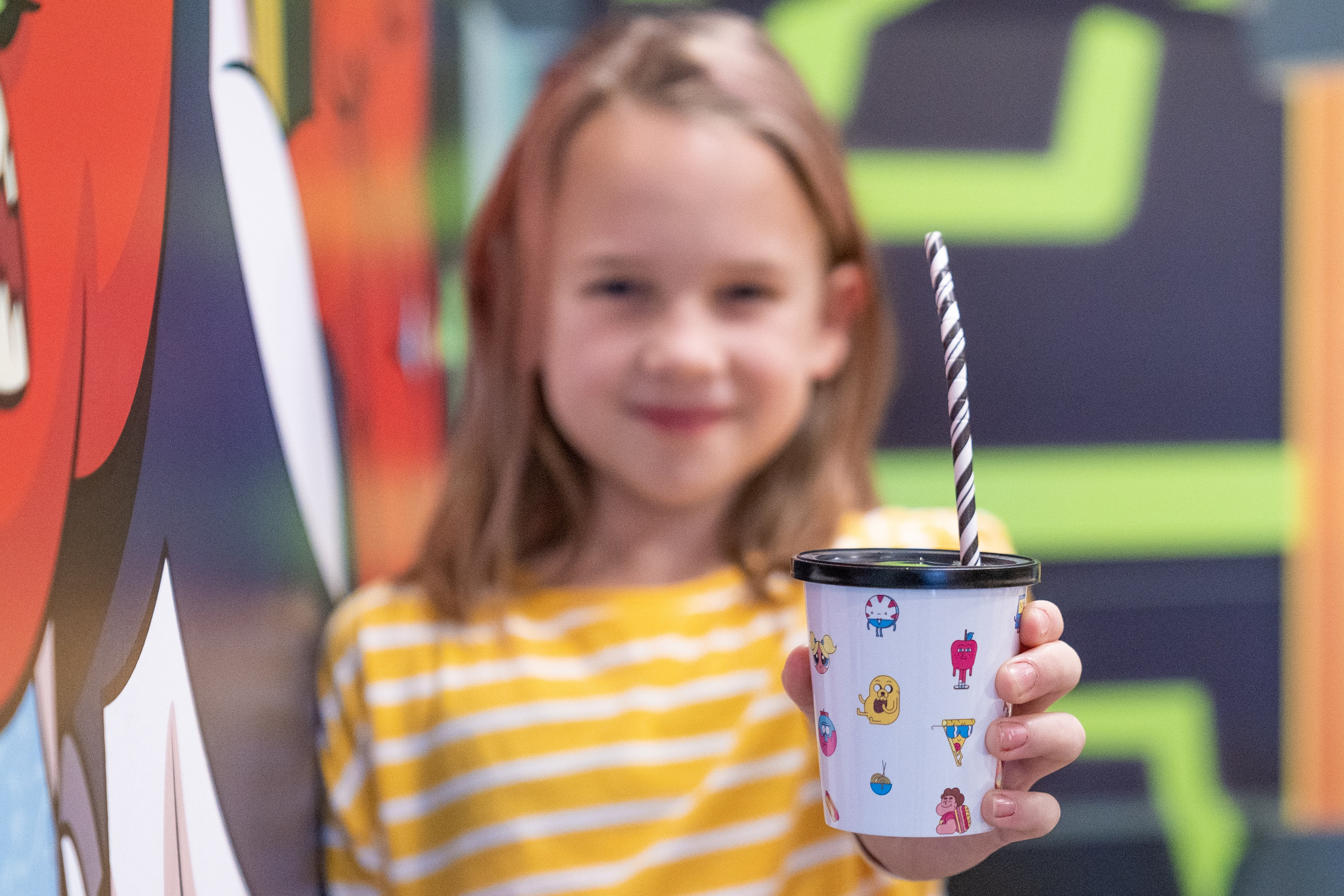 Girl holding a Cartoon Network themed drinking cup