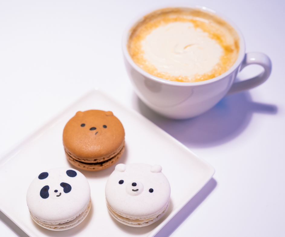 A latte and 3 macaroons in the shape of the We Bare Bears heads