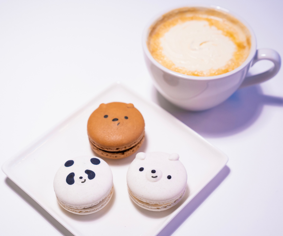 Bear shaped macaroons next to a latte cup