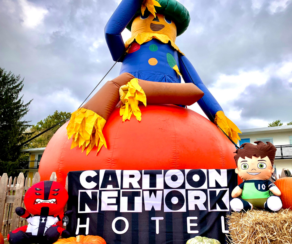 Ben 10 and Four Arms plush in front of a giant inflatable pumpkin and scarecrow
