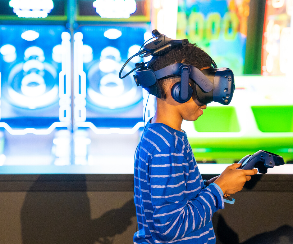 Boy wearing a VR headset and playing a VR game in an Omnicade VR pod