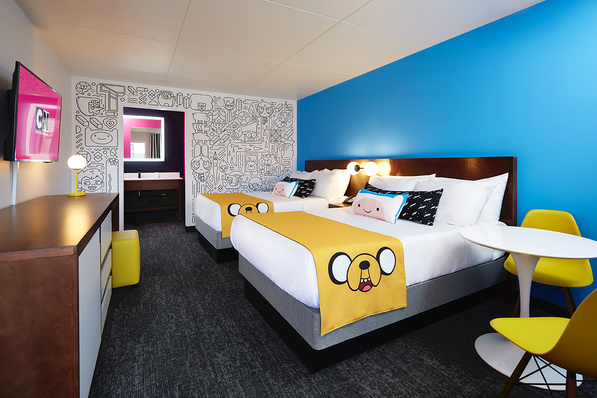 Two beds with Adventure Time cartoon theming sit inside a standard guest room at the Cartoon Network Hotel