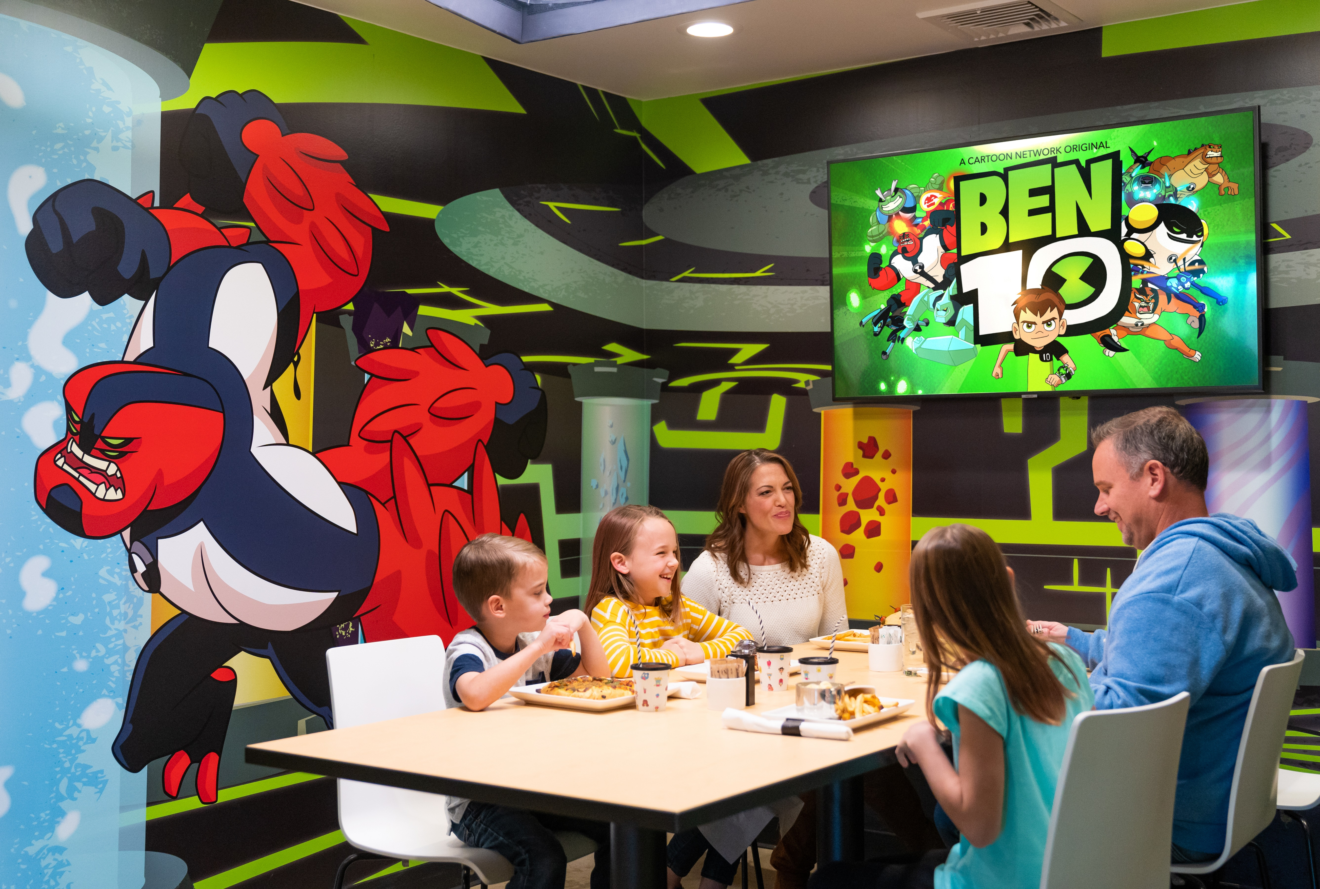 Family laughing and eating in a Ben 10 Dream Cube