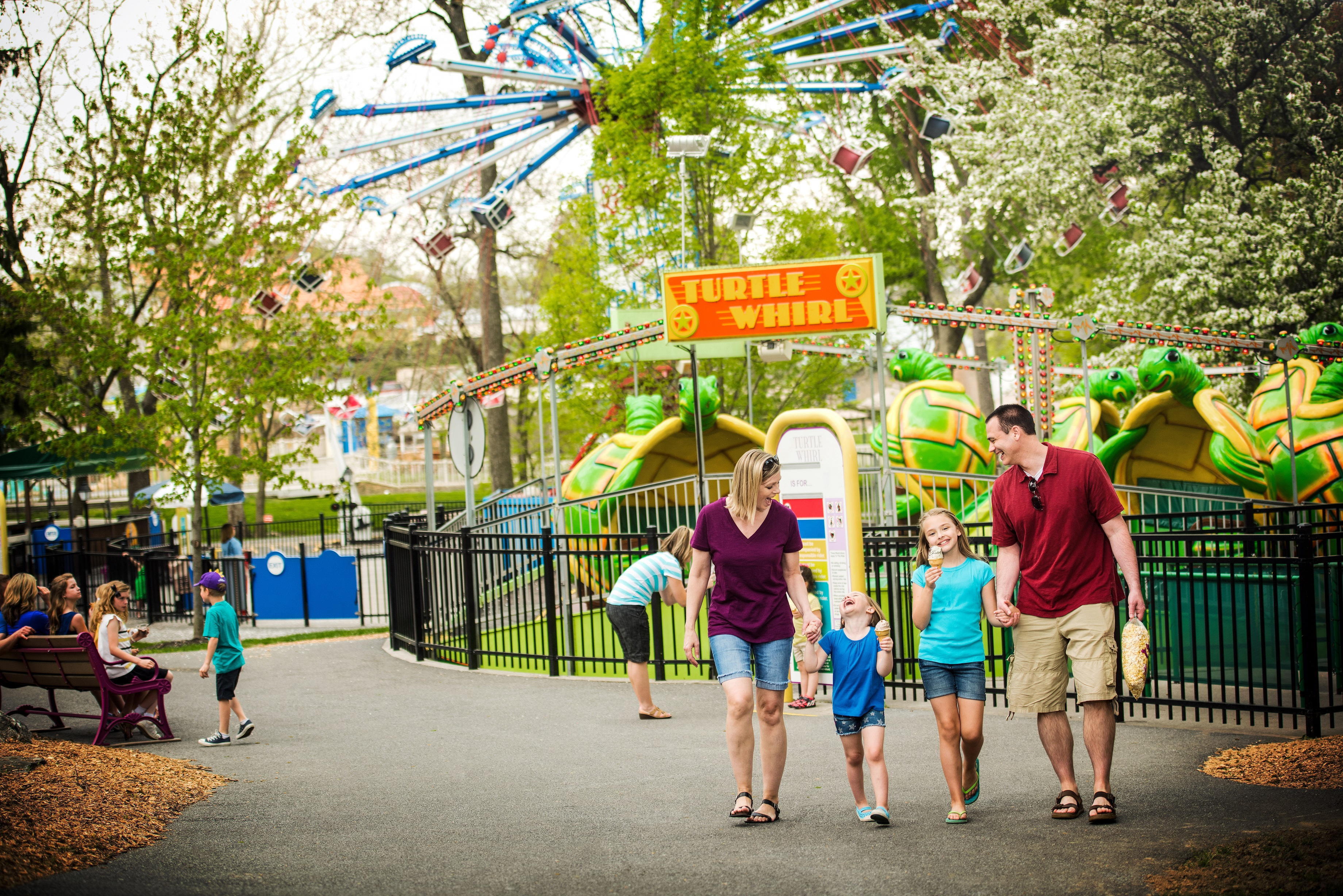 Family walking hand-in-hand through amusement park while the two young girls eat ice cream cones.