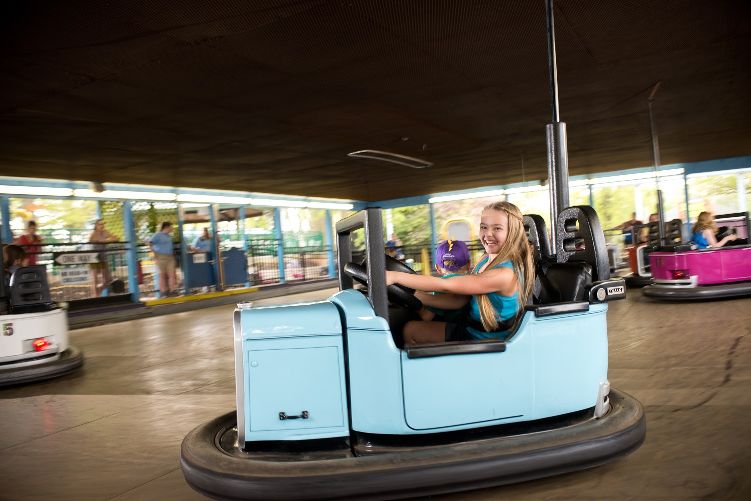 Girl driving bumper cars ride vehicle and smiling.