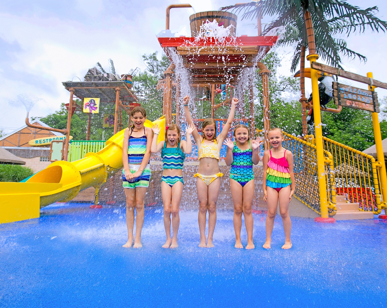 Five girls standing and smiling in front of tipping bucket water play area