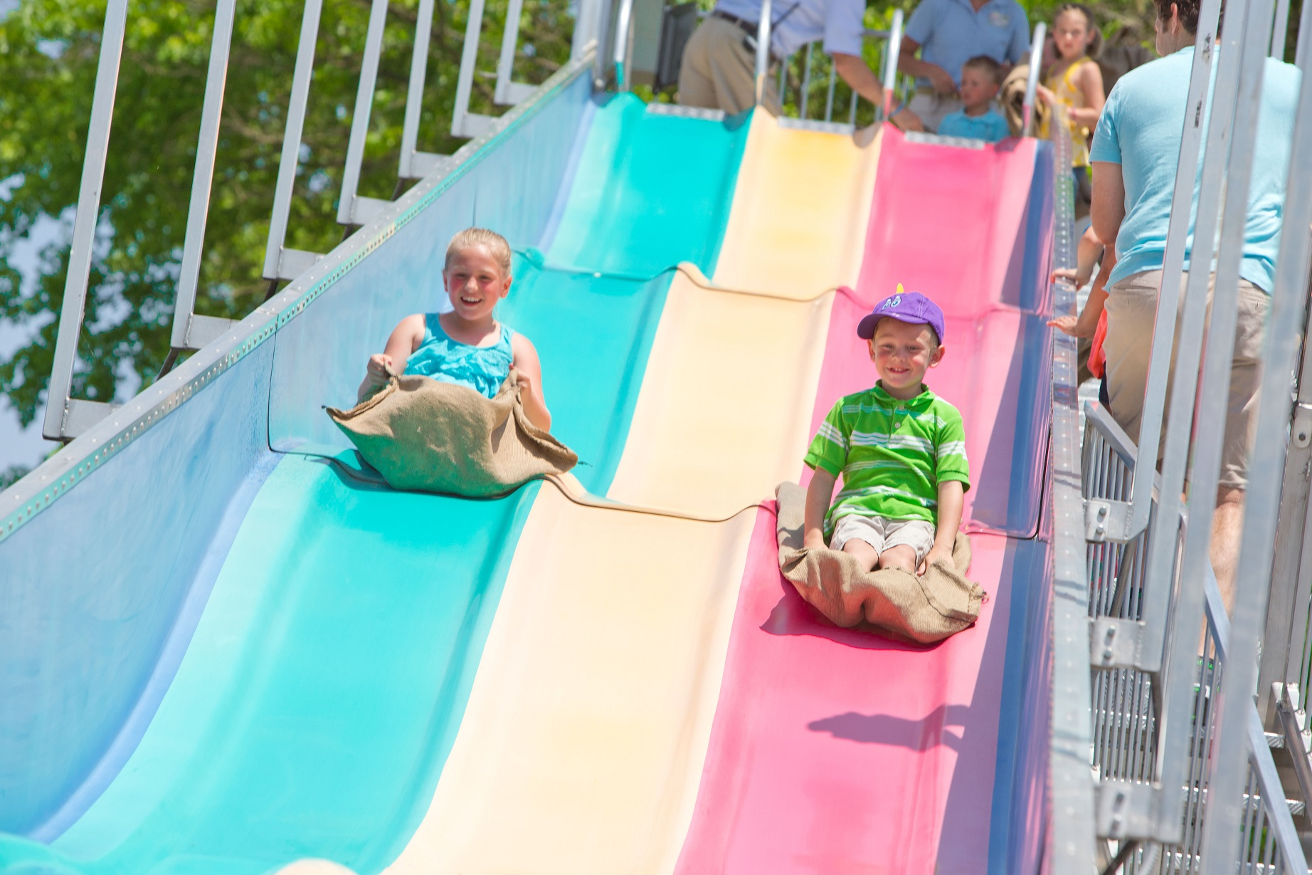 Children sliding down large multi-colored slide attraction.