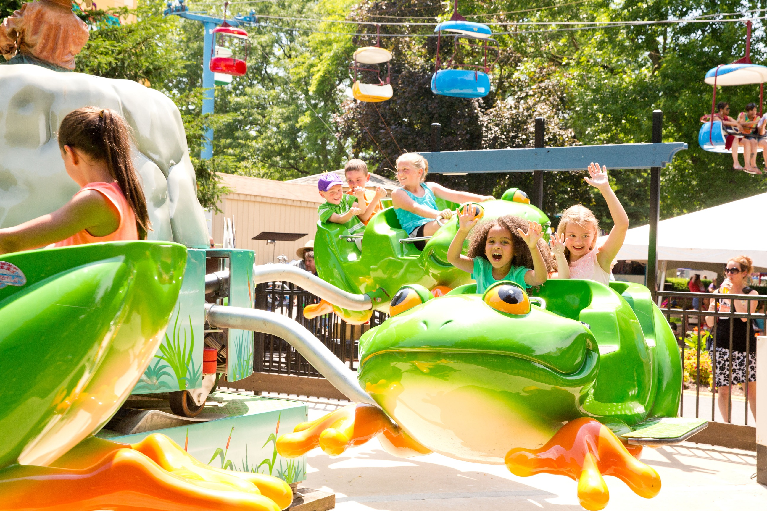 Children holding their hands in the air while riding attraction in frog-shaped cars.