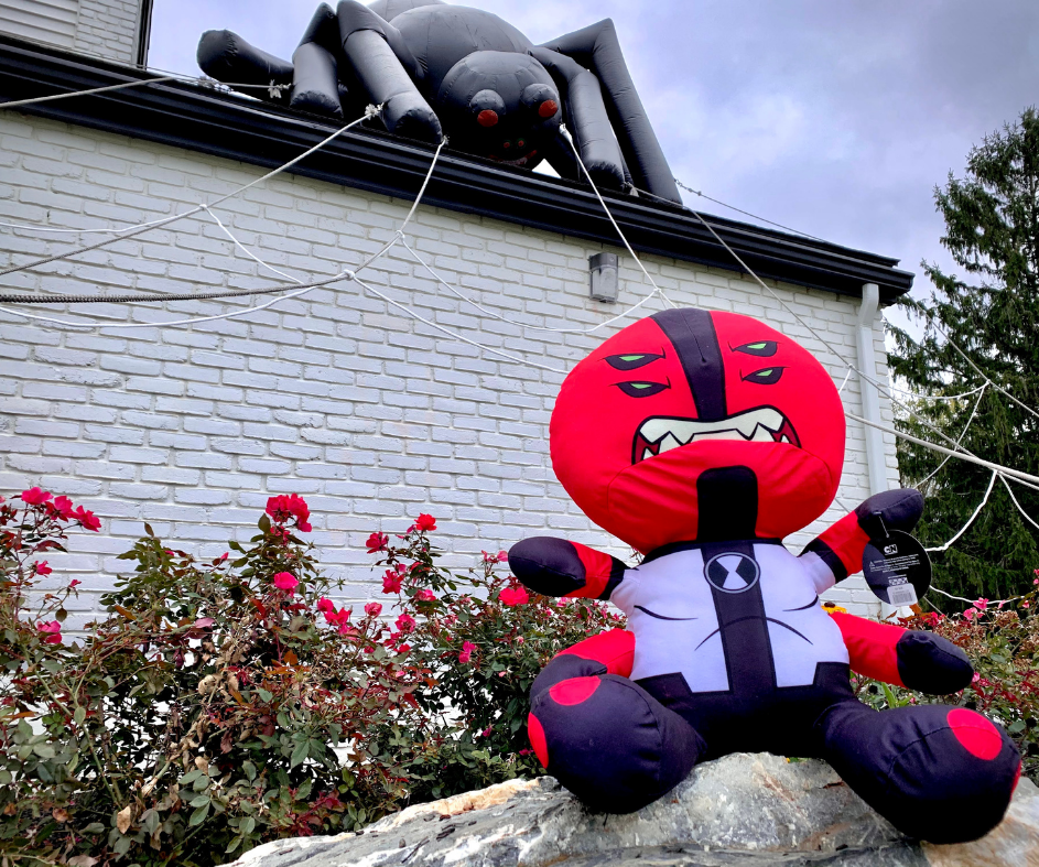 Ben 10's Four Arms alien plush in front of giant inflatable spider