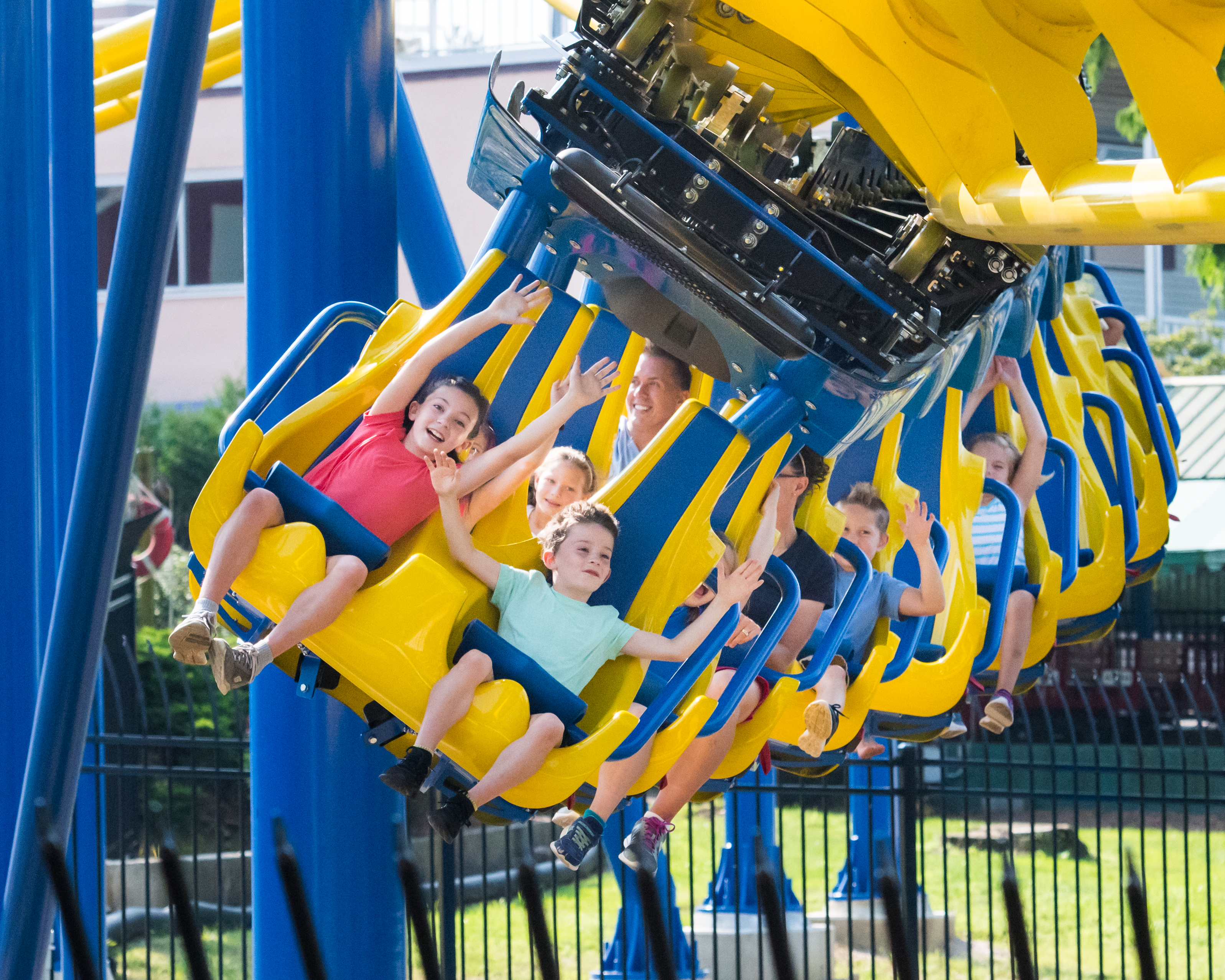 Two children riding in front row of yellow and blue suspended steel roller coaster.