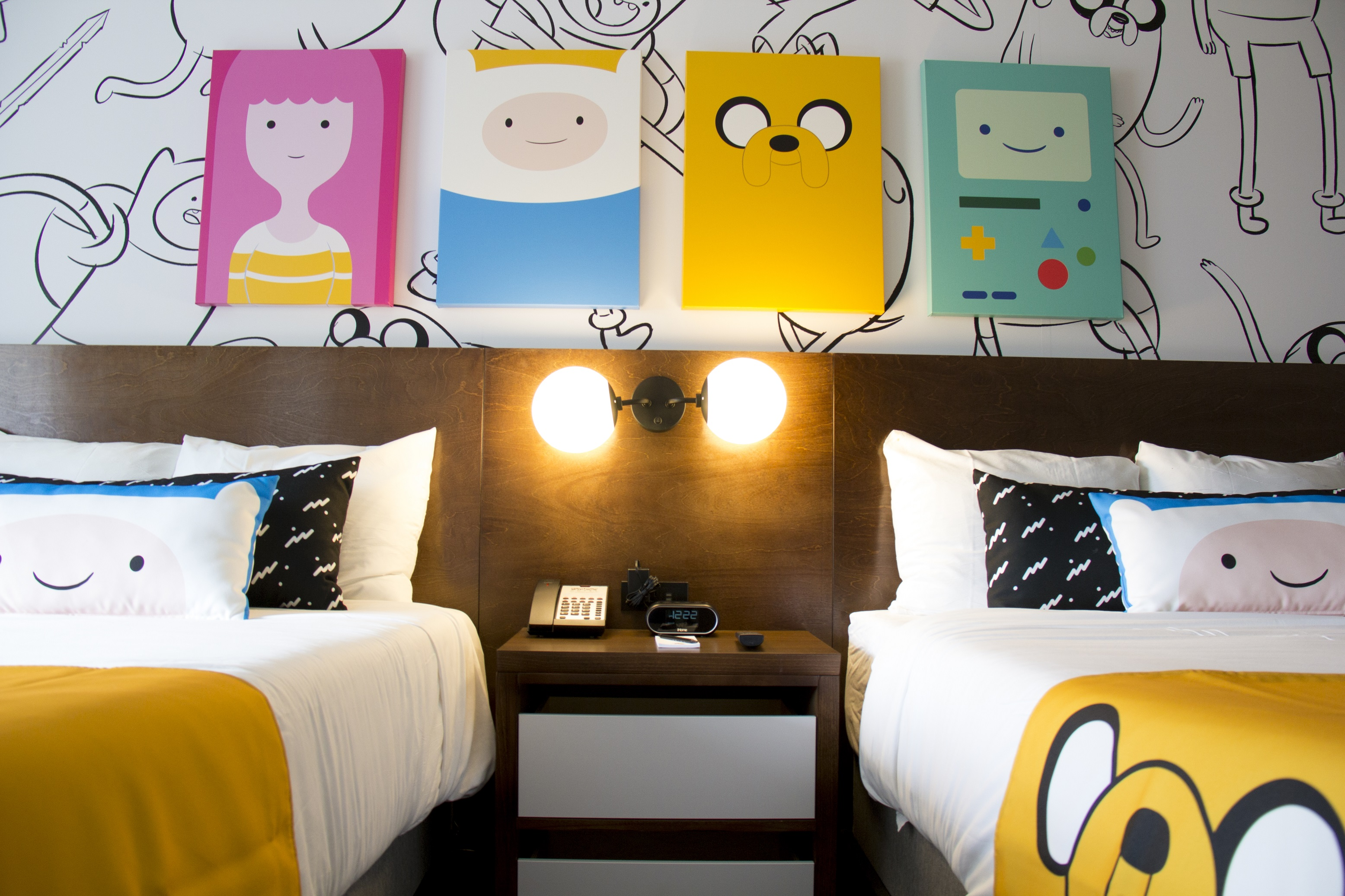 Adventure Time show themed canvases above two double beds