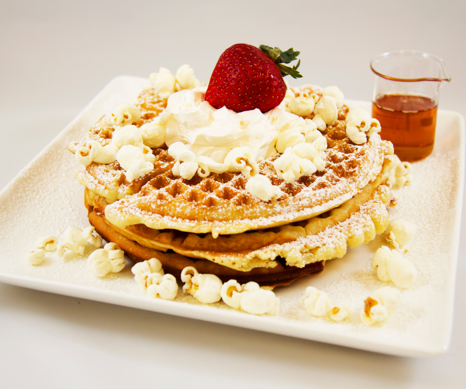 Waffles topped with popcorn, whipped cream, and a strawberry - the Together Breakfast